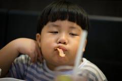 A boy eats bacon. A fat boy eats bacon in the Korean restaurant stock photos