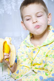 Boy eats a banana. Amusing face and thoughts about the passage of bananas Stock Photography