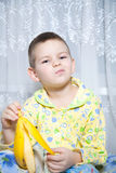 Boy eats a banana. How do we bring bananas? Very tasty bananas Stock Photography