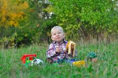Boy eats a banana and laughs Royalty Free Stock Photo