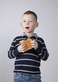 Boy eats bread Stock Images