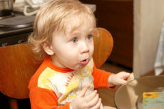 The boy eats bread. The hungry  boy eats bread at home Royalty Free Stock Image