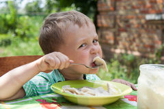 Boy eats breakfast outdoors Stock Photo