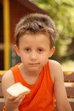Boy eats buttery bread Royalty Free Stock Photos
