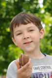 Boy eats chocolate egg and smiling Stock Photo