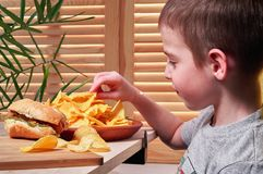 Boy eats delicious potato chips in cafe. Child holds the chips in his hand. On the table lies  bitten hot dog. Fast food. Stock Image