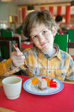 The boy eats dessert. The boy in restaurant with unpleasant face Stock Images
