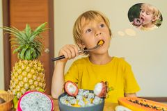Boy eats fruit but dreams about donuts. Harmful and healthy food for children. Child eating healthy snack. Vegetarian royalty free stock image