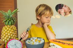 Boy eats fruit but dreams about hamburger. Harmful and healthy food for children. Child eating healthy snack. Vegetarian royalty free stock photo