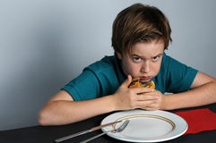 Boy eats hamburger. Boy worries about that someone could take away his hamburger royalty free stock photography