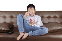 Boy eats ice cream on couch Stock Image