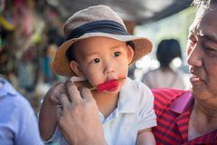 A boy eats ice cream. Grandpa is helping grandson, eats a ice cream Royalty Free Stock Images