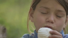 Boy eats marshmallows outdoors. Portrait of a white-skinned child with marshmallows in hand. stock footage