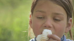 Boy eats marshmallows outdoors. Portrait of a white-skinned child with marshmallows in hand. stock video footage