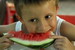 Boy eats melon Stock Photo