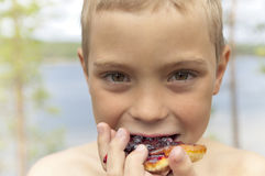 The boy eats pancakes with blueberry jam. Stock Photo