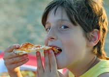 Boy eats pizza with potato chips on the beach Royalty Free Stock Photography