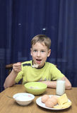 Boy eats a porridge with milk Stock Images