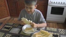 The boy eats an  tasty melon stock video