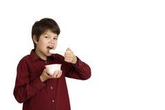 Boy eats yogurt Stock Image