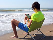 Boy with ebook and shorts on the beach in summer. Young boy with ebook and shorts on the beach in summer Stock Photo