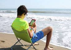 Boy with ebook and shorts on the beach. Young boy with ebook and shorts on the beach Royalty Free Stock Images