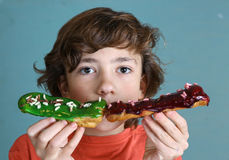 Boy with eclair french dessert in hands Royalty Free Stock Image
