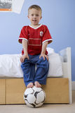 Boy (4-6) on edge of bed, feet on ball, smiling, portrait, low angle view Royalty Free Stock Photography