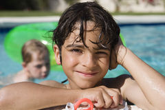 Boy At Edge Of Swimming Pool. Portrait of a happy little boy resting at edge of swimming pool Royalty Free Stock Images