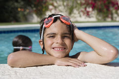Boy At The Edge Of Swimming Pool. Portrait of a happy little boy resting at the edge of the swimming pool Stock Images