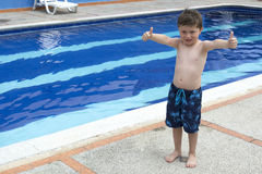 Boy at the edge of a swimming pool. Boy at the edge of an outdoor swimming pool Stock Photography