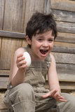 The boy with egg. The boy with big goose egg on porch of house Royalty Free Stock Images