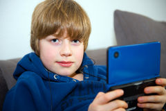 Boy with elektrinic game Royalty Free Stock Image