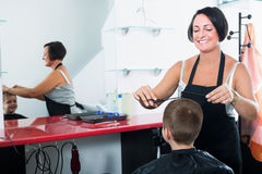Boy in elementary school age getting hairdo by female. Professional hairdresser in beauty salon Royalty Free Stock Image