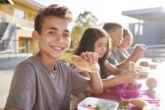 Boy at elementary school lunch table smiling to camera stock image