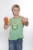 A boy of eleven years holds in hands  packing with vitamins. Background is white Royalty Free Stock Photo
