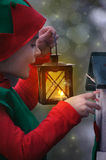 Boy in elf costume with lantern. Looking at birdhouse Stock Image