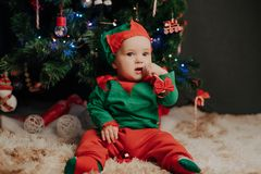 Boy in a elf costume sits under a Christmas tree with a Lollipop stock photography