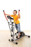 Boy on elliptical trainer laughing Royalty Free Stock Photos