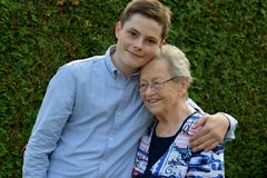 Boy embraces lovingly his great-grandma royalty free stock photography