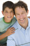 Boy embracing father, smiling, portrait, cut out.  stock photography