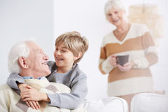 Boy embracing his grandfather. Grandmother and happy boy embracing his beloved grandfather Stock Photography