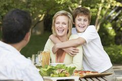 Boy Embracing His Mother. Happy teenage boy embracing his mother from back stock photography