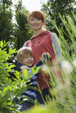 Boy Embracing Mother In Garden. Portrait of smiling women embracing son in the garden royalty free stock image