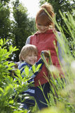 Boy Embracing Mother In Garden. Portrait of smiling women embracing son in the garden stock photography