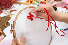 Boy embroidered on the hoop, hand closeup and red ribbon on white textile, learns to sew, job training, handmade and handicraft co. Ncept royalty free stock photo