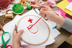 Boy embroidered on the hoop, hand closeup and red ribbon on white textile, learns to sew, job training, handmade and handicraft co. Ncept royalty free stock images