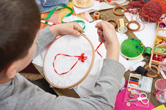 Boy embroidered on the hoop, hand closeup and red ribbon on white textile, learns to sew, job training, handmade and handicraft co Royalty Free Stock Photography