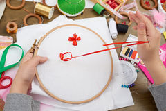 Boy embroidered on the hoop, hand closeup and red ribbon on white textile, learns to sew, job training, handmade and handicraft co Stock Images