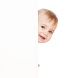 Boy emerge from behind poster. Royalty Free Stock Photo